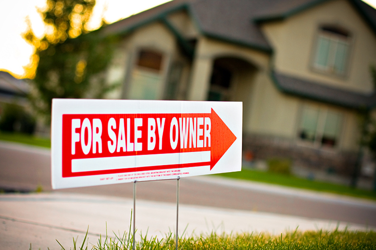 a For Sale By Owner sign in a front yard