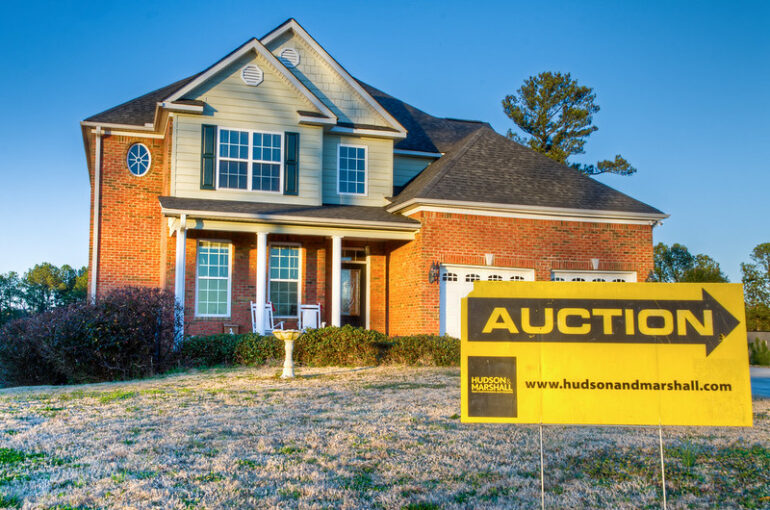auction sign in front of foreclosed home
