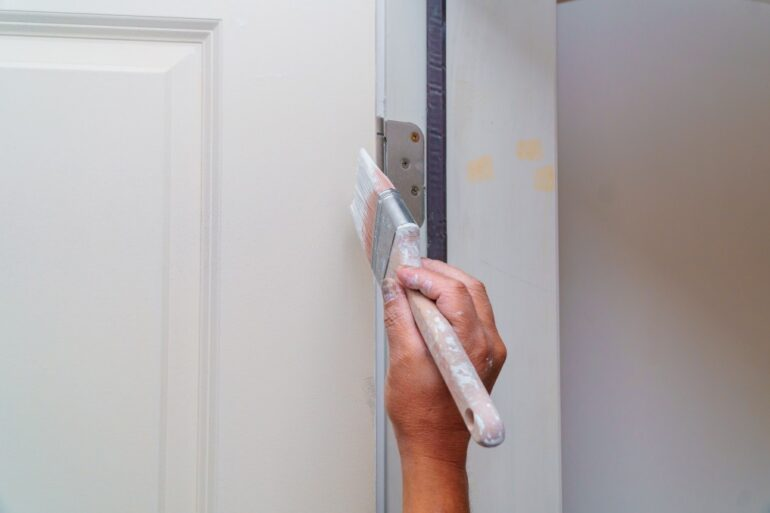 man painting a door white