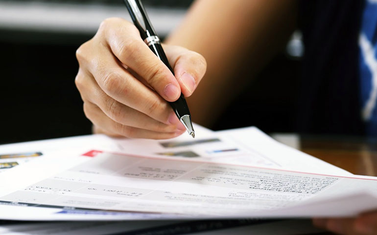 woman signing legal documents to take ownership of the house she has inherited