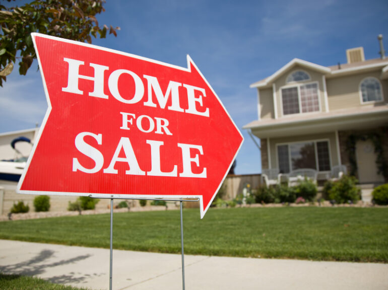 a home for sale sign in a front yard