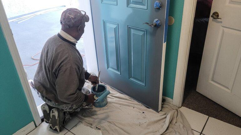 man painting a front door