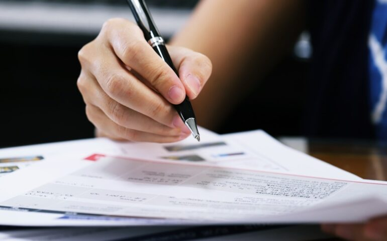 woman signing a mortgage refinance document
